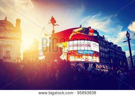 LONDON - JUNE 25: Vintage style artistic photograph of Piccadilly Circus neons at sunset, young night. This place is of the major tourist attractions on June 25, 2015 in London, UK.