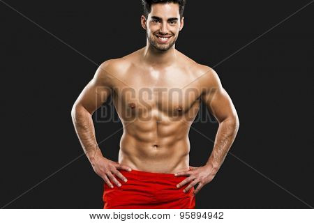 Portrait of a handsome and sexy muscular man, isolated over gray background