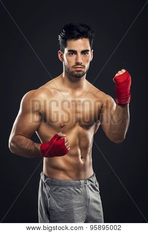 Portrait of a young male Body Combat atlhlete, isolated over a dark background