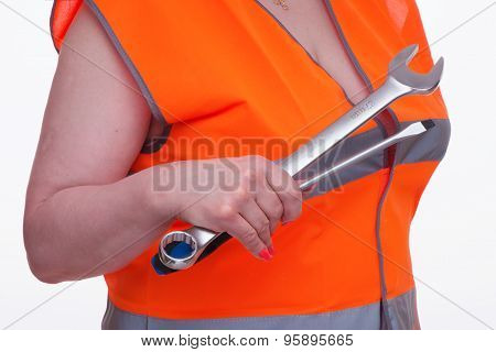 Woman In Orange Vest Holds Tools In Hand