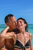 image of crystal clear  - Loving and sensual couple kissing on a beautiful deserted beach with turquoise and crystal clear waters of the Caribbean sea in the Dominican Republic on the island of Saonna - JPG