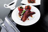 stock photo of braai  - fresh red beef meat steak barbecue garnished vegetable salad and basil on white plate over black wooden table with bbq sauce in sauceboat - JPG