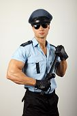 picture of policeman  - Portrait of policeman in sunglasses holding nightstick - JPG
