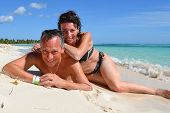 stock photo of crystal clear  - Happy loving couple on a beautiful deserted beach with turquoise and crystal clear waters of the Caribbean sea in the Dominican Republic on the island of Saonna - JPG