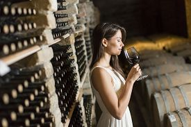 pic of wine cellar  - Young woman with a glass of wine in the wine cellar - JPG