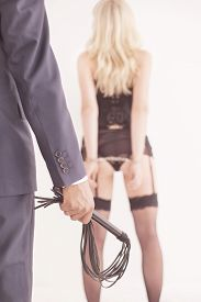 picture of domination  - Leather whip held by dominant master in suit ans woman waiting - JPG