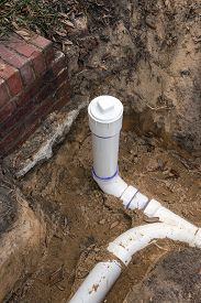 stock photo of pipe-welding  - New PVC pipe sewer line and clean out installed in trench - JPG