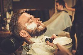 stock photo of barber razor  - Client during beard shaving in barber shop - JPG