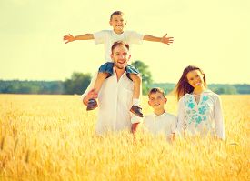 stock photo of mother baby nature  - Happy Young Family with two children walking on wheat summer field - JPG