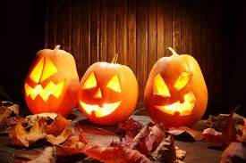 pic of jack o lanterns  - Jack o lanterns Halloween pumpkin face on wooden background and autumn leafs - JPG