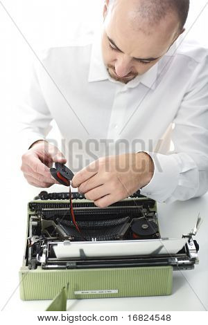 man try to fix vintage typewriter selective focus image