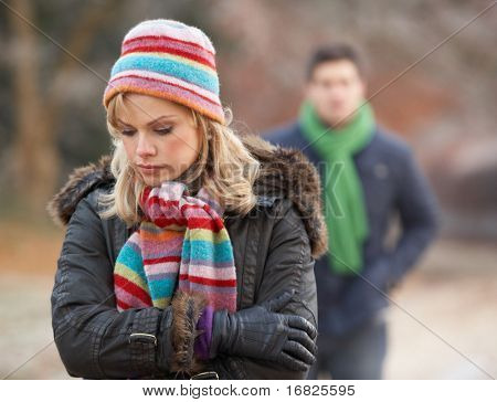 Couple On Winter Walk Through Frosty Landscape