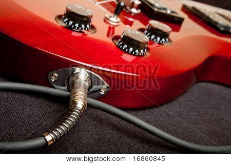 Detail of a wine red color electric guitar with cord plugged into the jack.