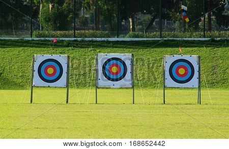 Three archery targets in a row in a grass field on a sunny day