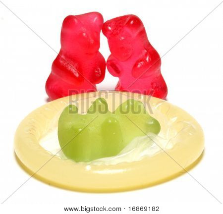 Red jelly bears parent and green jelly bear baby on a condom - conceptual image - on white background