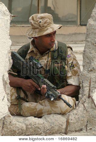 British Soldier Against A Damaged Building In Iraq.
