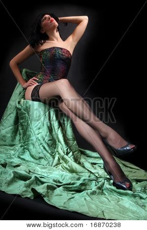 Beautiful brunette woman in black nylons posing on a green vintage background. Studio shot.