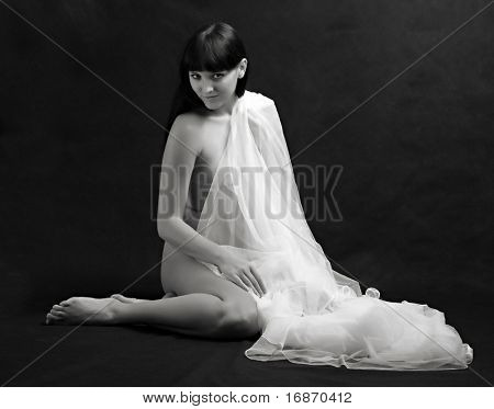 Naked sexy beautiful slenderness young woman in bridal veil on black background. Monochrome studio shot. Great for calendar.