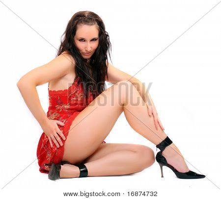 Sitting flirty girl with long slim legs. Studio shot.