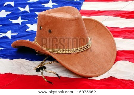 Brown leather hat on american flag. Traditional hat for all american cowboys. Great image for Independent Day brochures and advertising.