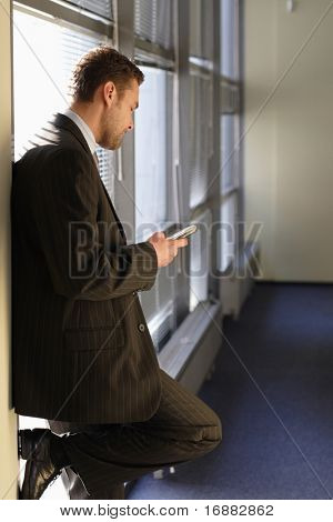 standing business man dialing ion phone in sunny room