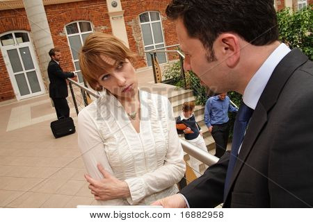 Man and woman in professional attire having a discussion outside of a public building. Woman's expression and body language is serious, possibly unhappy.