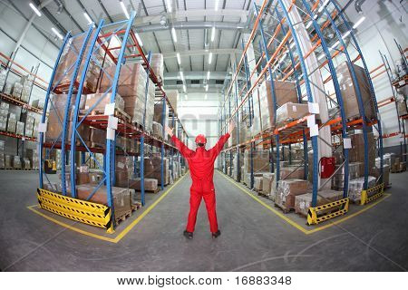 worker in red uniform raising hands in the middle of warehouse