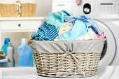 Clothes in wicker basket at laundry poster