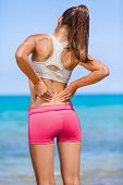 Fitness back pain. Athlete woman from behind on beach touching painful side muscles, rubbing the mus poster