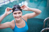Pretty woman wearing swim cap and swimming goggles at the pool poster