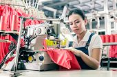 Seamstress or worker in Asian textile factory sewing with  industrial sewing machine poster