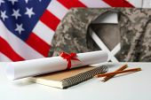 Notebook, diploma and pencils on white table. USA military education concept poster
