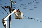 image of cherry-picker  - Worker in cherry picker fixing power lines - JPG