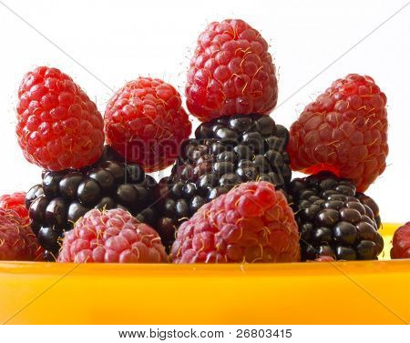blackberries and raspberries in orange pot