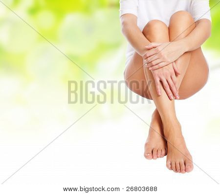 Female Legs Being Massaged Over Green Spring Background