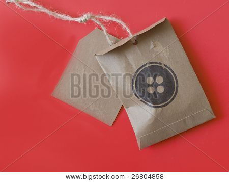 price tag and bag for buttons on red background