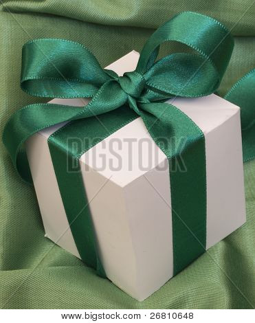 gift box with the beautiful sateen bow on the silk background