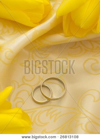 golden wedding rings on the yellow textile background