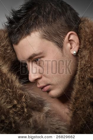 Close-up of  handsome  young man wearing in fur coat
