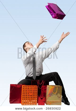Handsome young man with many shopping bags against blue background