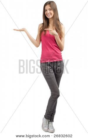Portrait of a happy casual girl showing something on the palm of her hand and pointing, against white background