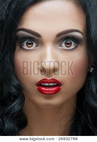 close up Studio Portrait of beautiful young Woman with helle Make-up und Frisur looking surprised