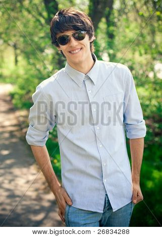 Handsome young man wearing casual walking in park and smiling