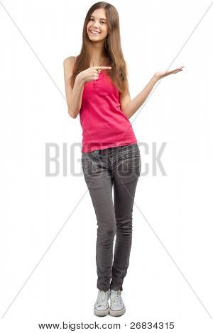 Full length portrait of beautiful casual girl pointing and showing something on the palm of her hand. Isolated on white background.