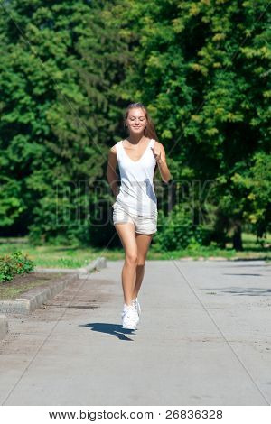 Young beautiful woman running in summer park