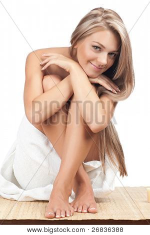 Portrait of young beautiful woman wearing towel and sitting on bamboo mat at spa salon