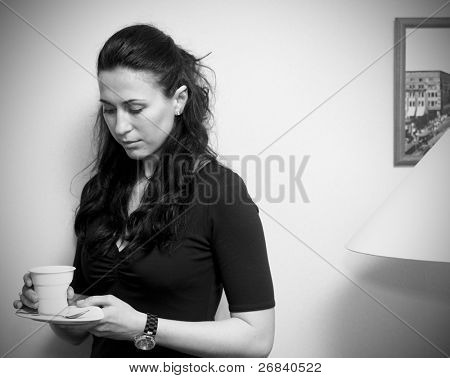 Thoughtful woman with cup of coffee, hard light, vignetting added