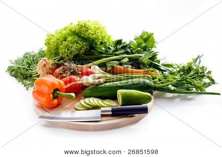 Raw vegetables on cutting board on white background