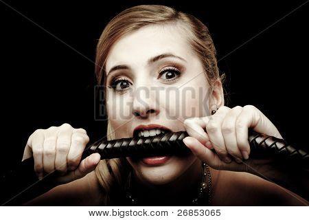 glamorous girl bites whip on dark background