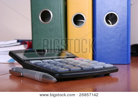 accountant desk with clip folders and calculator